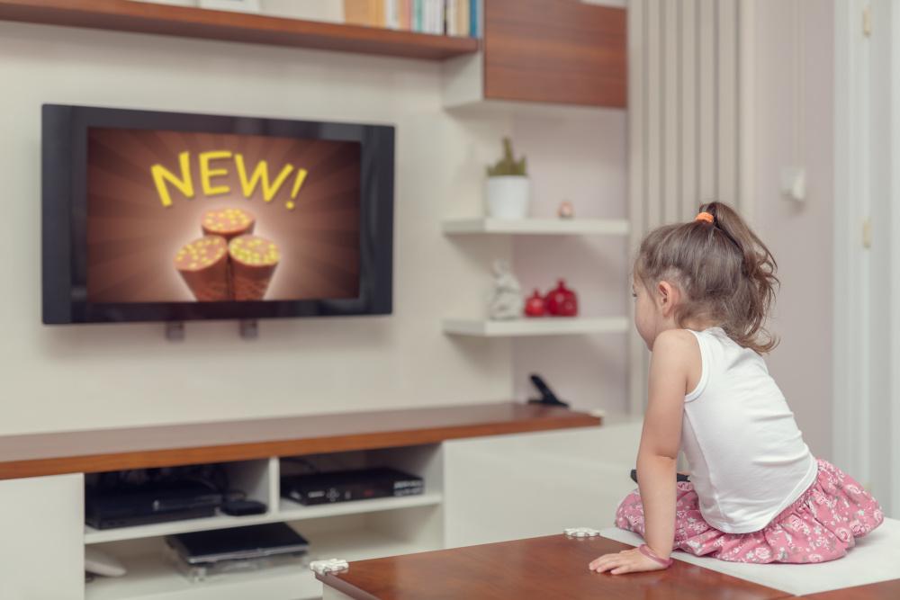 mała dziewczynka siedząca przed ekranem telewizora