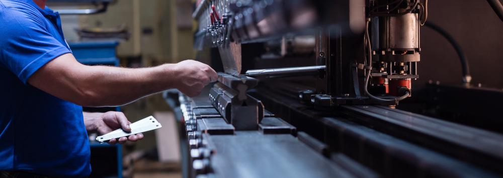 pracoenik który obrabia metale na maszynie