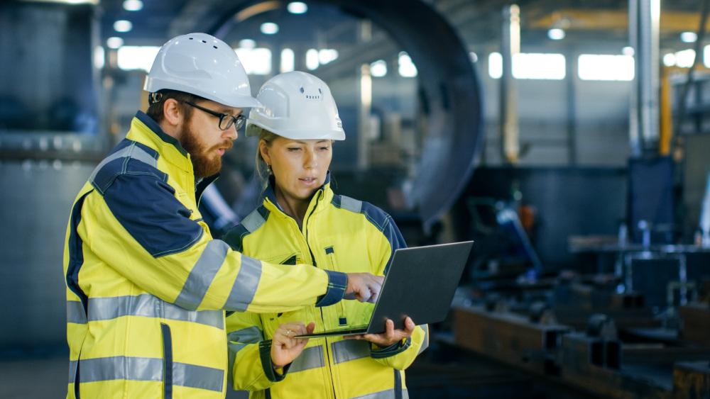 kobieta i mężczyzna w strojach roboczych korzystają z laptopa