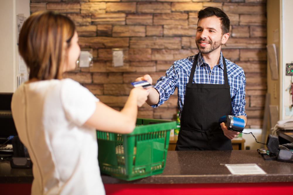 mężczyzna obsługujący kobietę w sklepiku